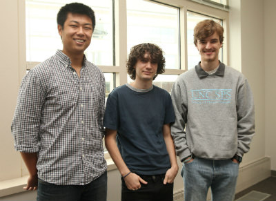 Three student developers pose