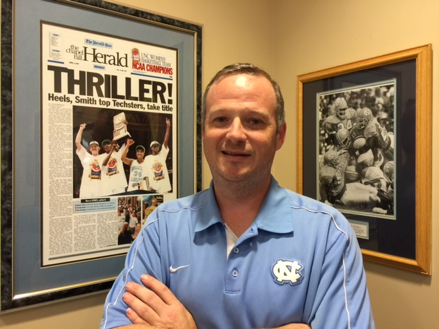 Tom Livers poses with framed newspaper front pages of sports team wins