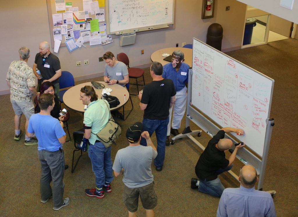 BarCamp attendees chat while topics are finalized