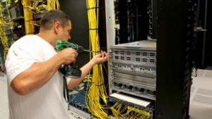 Communication Technologies employee installs Cisco core router