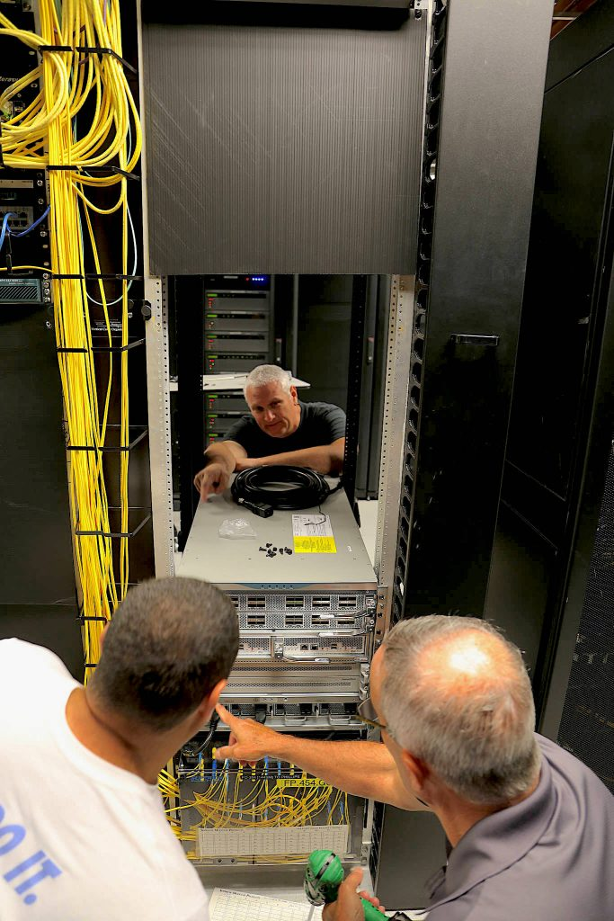 ITS Infrastructure & Operations employees rack the new Cisco Nexus at ITS Franklin.