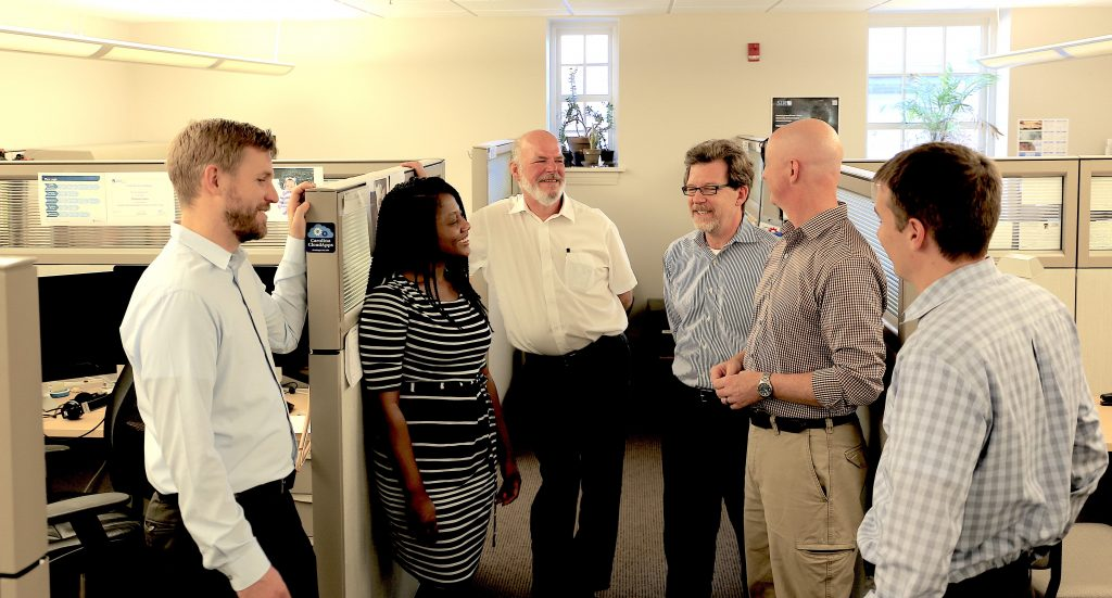 Six members of the Information Security Office talk in their workspace.