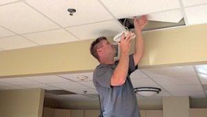 Worker installs Wi-Fi connection in ceiling at RAM Village