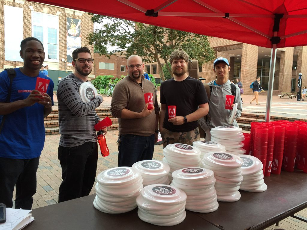 Five students show the freebies they picked up at Adobe Red Tent Day.