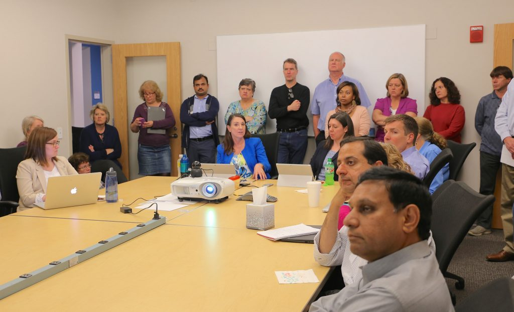 ITS staff crowd a conference room listening to a presentation.