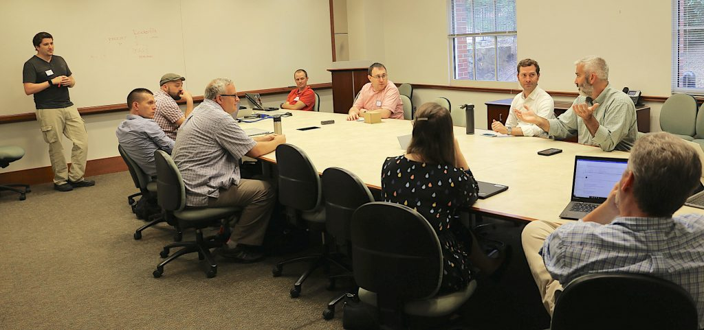 Participants converse around a conference table at one of the breakout sessions.