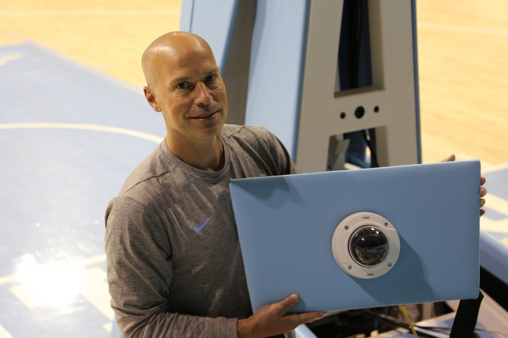 Assistant Coach Mike Schall holds an IP camera in Carmichael Arena