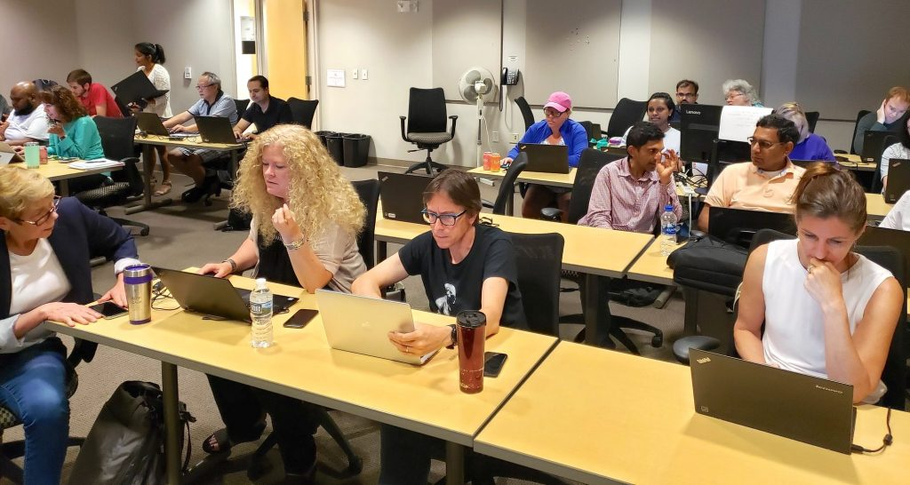 Enterprise Applications staffers work on their laptops and collaborate in a meeting room