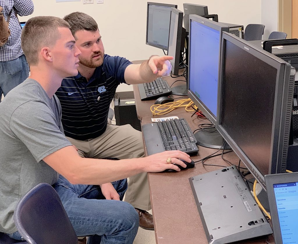 An ITS employee assists a SecurityCon participant on an activity on a computer