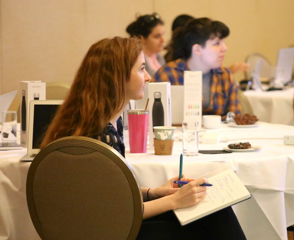 An attendee listens with her notebook at the ready