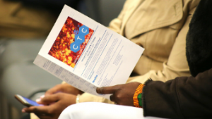 A hand holds a CTC program guide