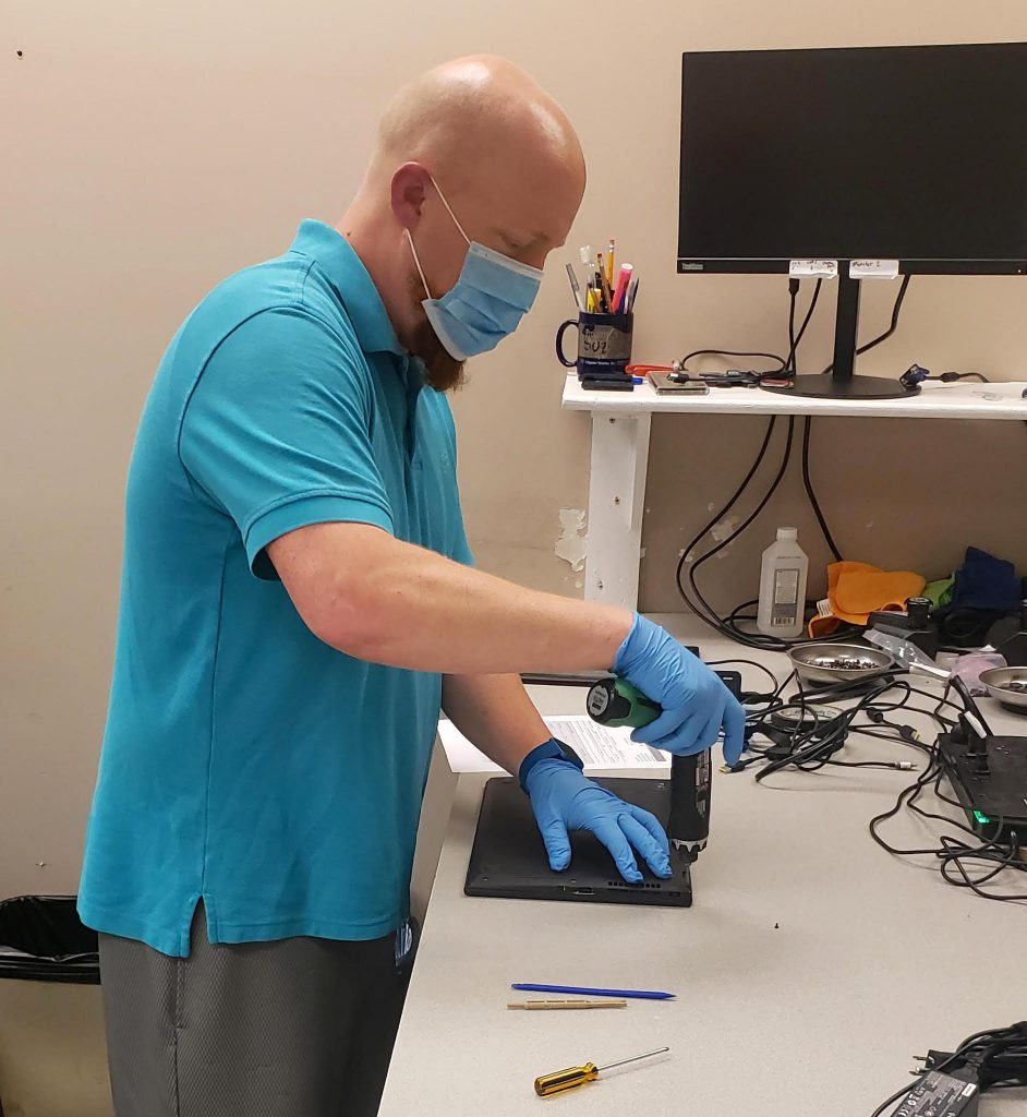 Wearing a mask and gloves, an employee uses a power screwdriver on a laptop