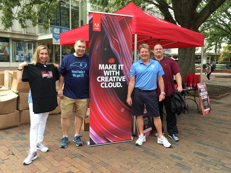 Greg Neville and Mike Roberts, then with Software Acquisition, pose with the Adobe reps at the 2016 Adobe Red Tent DayTent