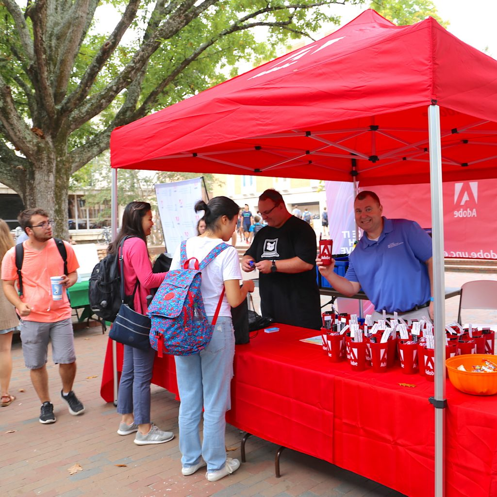Greg Neville shows off Adobe cup while staffing the Adobe tent at the tech fair in the Pit