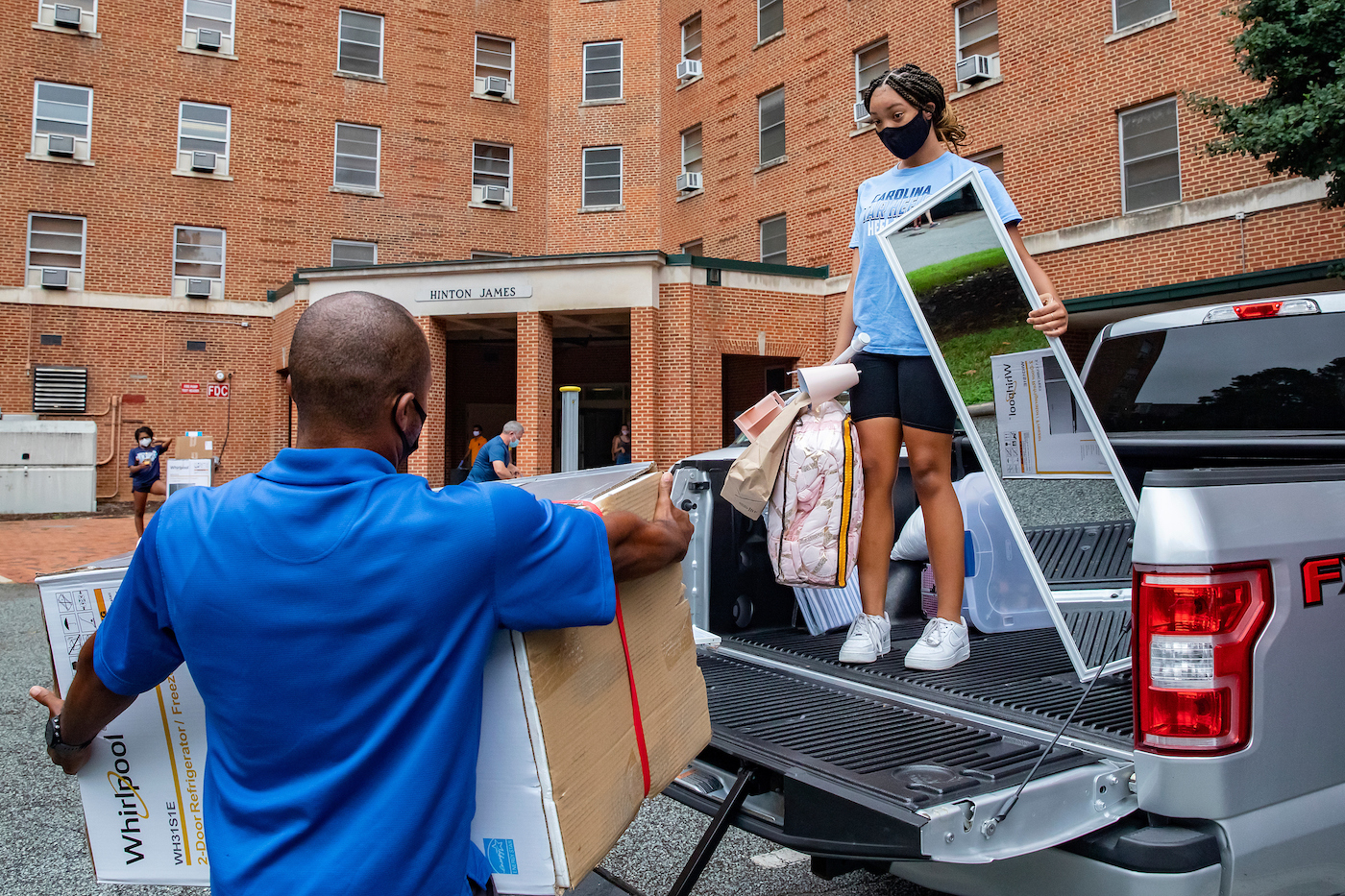 A man helps a student unload belongings from a pickup to move into Hinton James dorm.