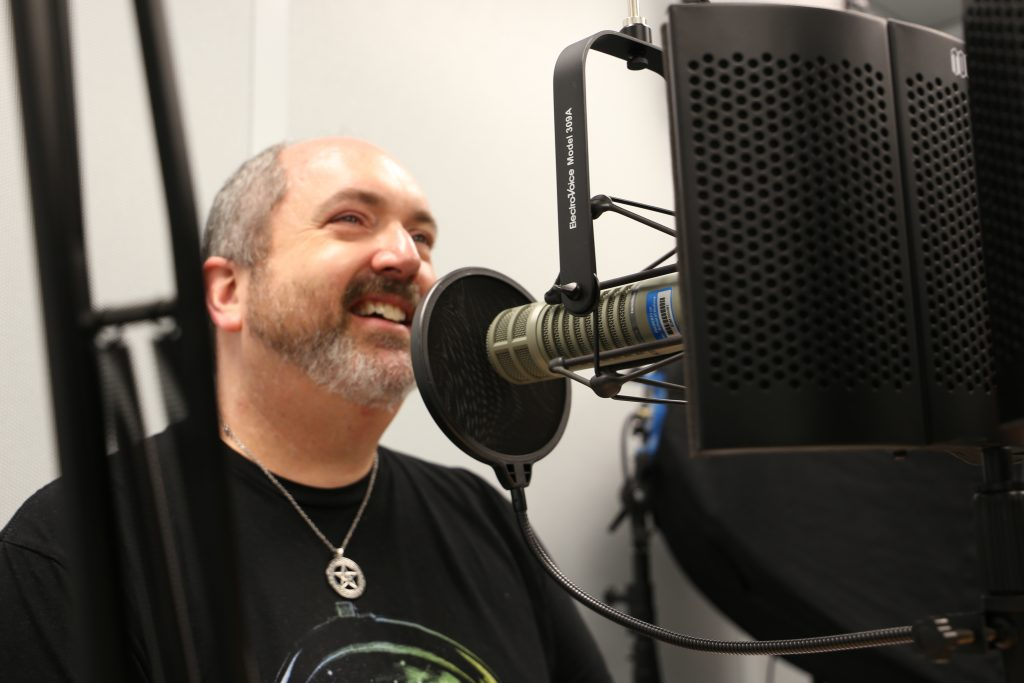 Micheal Williams speaks into microphone as he records podcast