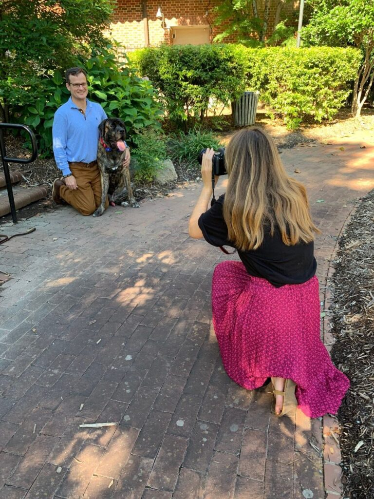Anne Claire Foreman photographs J. Michael Barker with his dog in the ITS Franklin courtyard