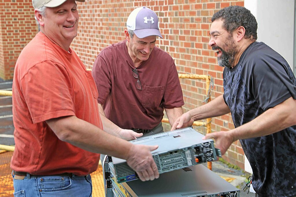 Mike Harris, Charles Woody and Mike Whitfield move computing equipment in March 2020