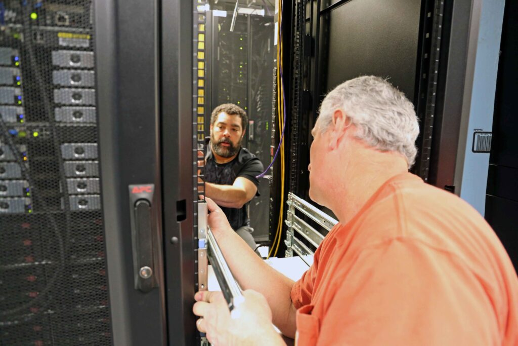 Mike Whitfield and Mike Harris install equipment in a data center