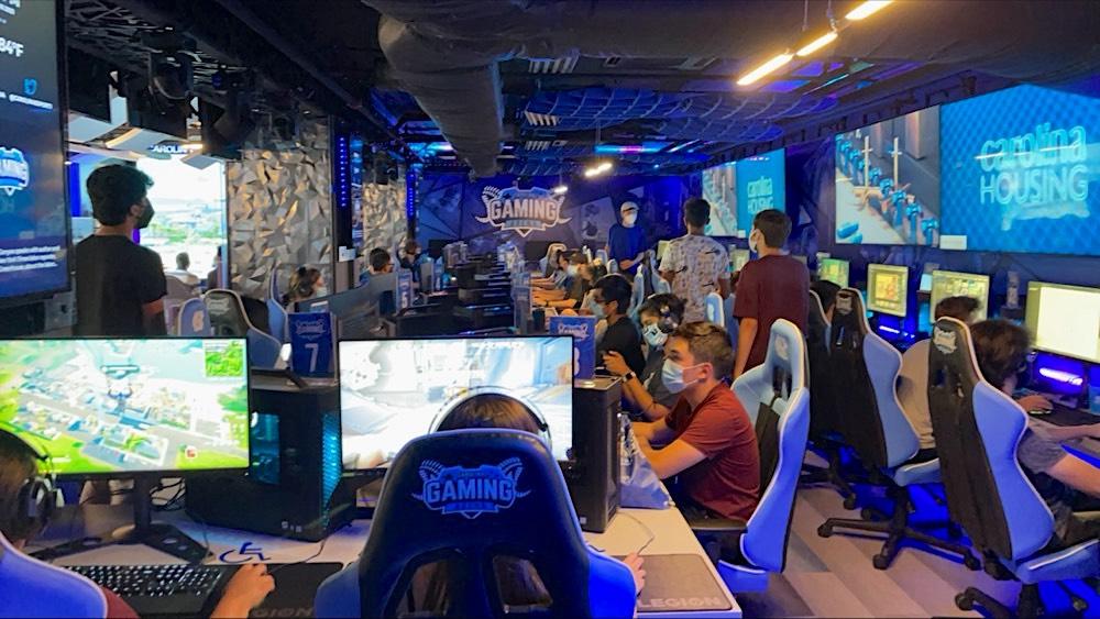 Wearing masks, sitting gamers play on individual computer screens